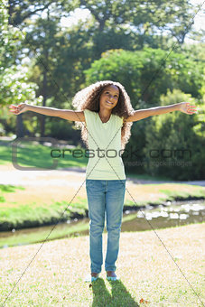 Young girl smiling with arms outstretched in the park