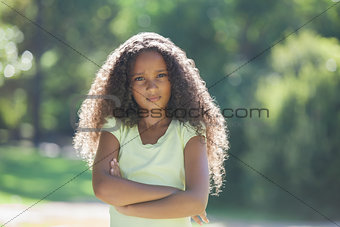 Young girl frowning at camera in the park