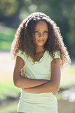 Young girl frowning with arms crossed in the park