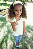 Young girl frowning and pointing at the camera in the park