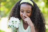 Young girl holding a flower and covering her nose in the park