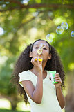 Young girl blowing bubbles in the park