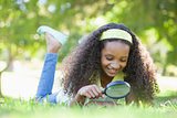 Young girl looking at grass through magnifying glass in the park