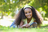 Young girl holding magnifying glass in the park smiling at camera