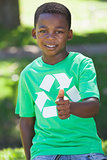 Young boy sitting on grass in recycling tshirt showing thumb up