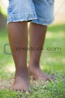 Little boys legs standing on grass