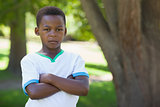 Little boy frowning at camera with arms crossed in the park