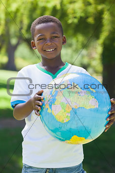 Little boy smiling at camera holding globe in the park