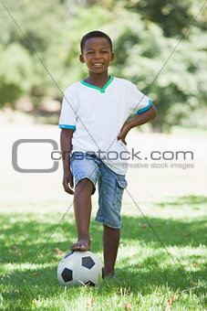 Little boy standing with football in the park