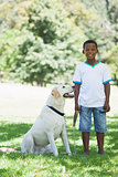 Little boy standing with his pet labrador in the park