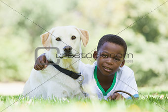 Little boy lying with his pet labrador in the park