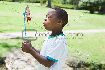 Little boy blowing pinwheel in the park