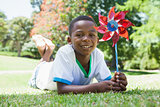 Little boy holding pinwheel in the park smiling at camera