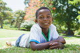 Little boy lying in the park smiling at camera