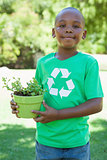 Little boy in recycling tshirt holding potted plant