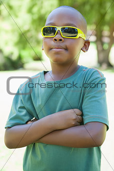 Cool little boy in sunglasses with arms crossed