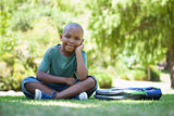 Happy schoolboy smiling at camera sitting on grass