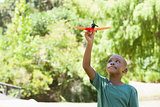 Happy little boy flying toy airplane