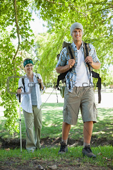 Happy active couple going on a hike smiling at camera