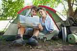 Cute couple sitting by tent reading a map