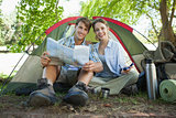 Cute couple sitting by tent reading a map smiling at camera
