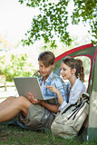 Cute couple sitting in their tent looking at laptop