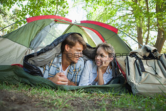 Cute couple lying in their tent smiling at each other