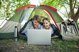 Cute couple lying in their tent using laptop