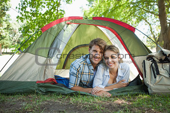 Cute couple lying in their tent smiling at camera