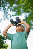 Little boy looking up through binoculars in the park