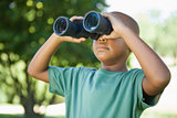 Little boy looking up through binoculars in the park