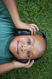 Little boy lying on grass listening to music smiling at camera