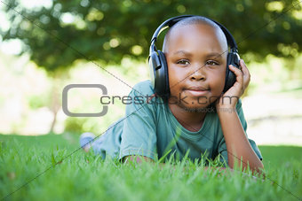 Little boy lying on grass listening to music and smiling
