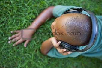 Little boy lying on grass listening to music
