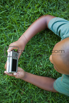 Little boy lying on grass looking at digital camera