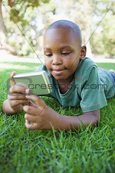 Little boy lying on grass looking at digital camera