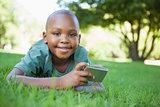 Little boy lying on grass holding digital camera smiling at camera