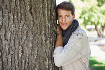Handsome man leaning against tree smiling at camera