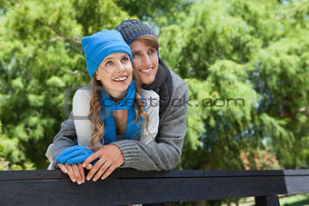 Cute couple standing in the park embracing by a fence