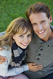 Cute couple sitting in the park embracing smiling at camera
