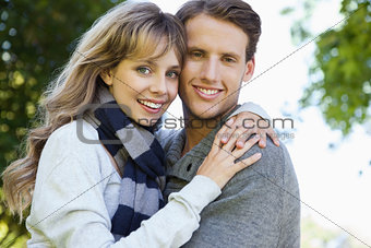 Cute couple embracing and smiling at camera in the park