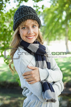 Pretty blonde in hat and scarf smiling at camera in the park