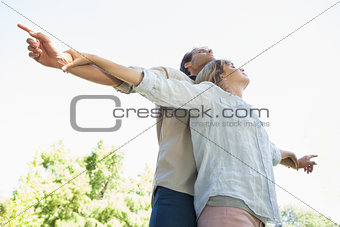 Carefree couple standing with arms out in the park
