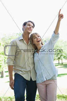 Carefree couple standing in the park with woman pointing