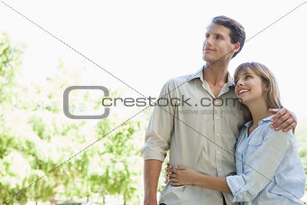Carefree couple standing in the park and hugging