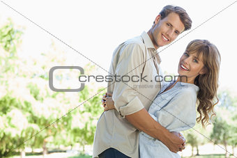 Carefree couple standing in the park and hugging smiling at camera