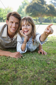 Carefree couple lying in the park with woman pointing