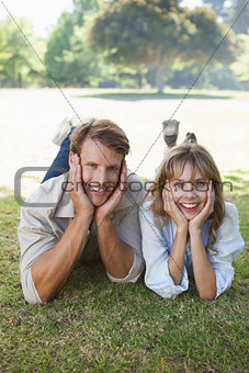 Carefree couple lying in the park smiling at camera