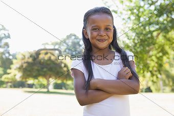 Little girl smiling at camera with arms crossed in the park