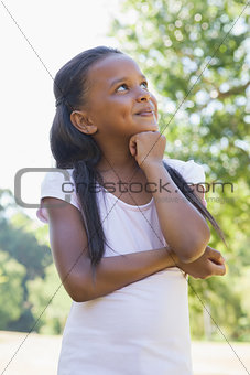 Little girl thinking with arms crossed in the park